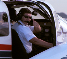 Shot of Aerosim flight instructor taxiing by with a thumbs up out of the door of a Piper Seminole.